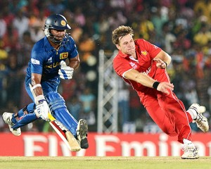Zimbabwe cricketer Kyle Jarvis (R) throws the ball as Sri Lankan cricketer Kumar Sangakkara (L) runs between the wickets
