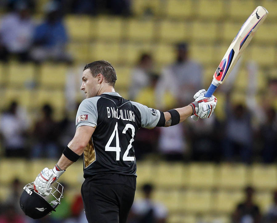 Brendon McCullum raises his bat to celebrate scoring a century during the ICC Twenty20 Cricket World Cup