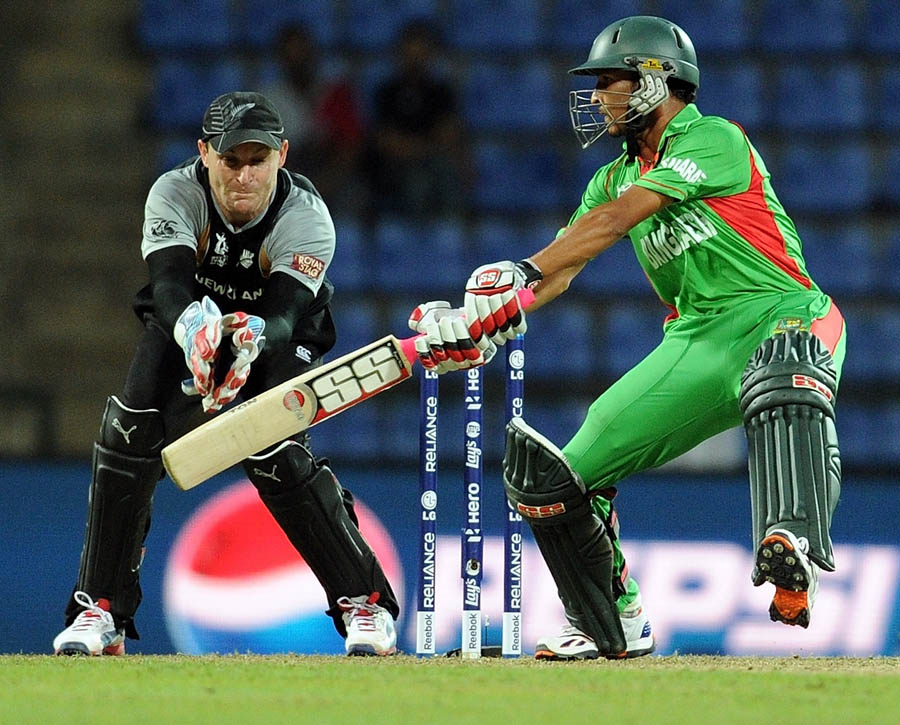 wicketkeeper Brendon McCullum (L) watches as Bangladesh batsman Nasir Hossain plays a shot
