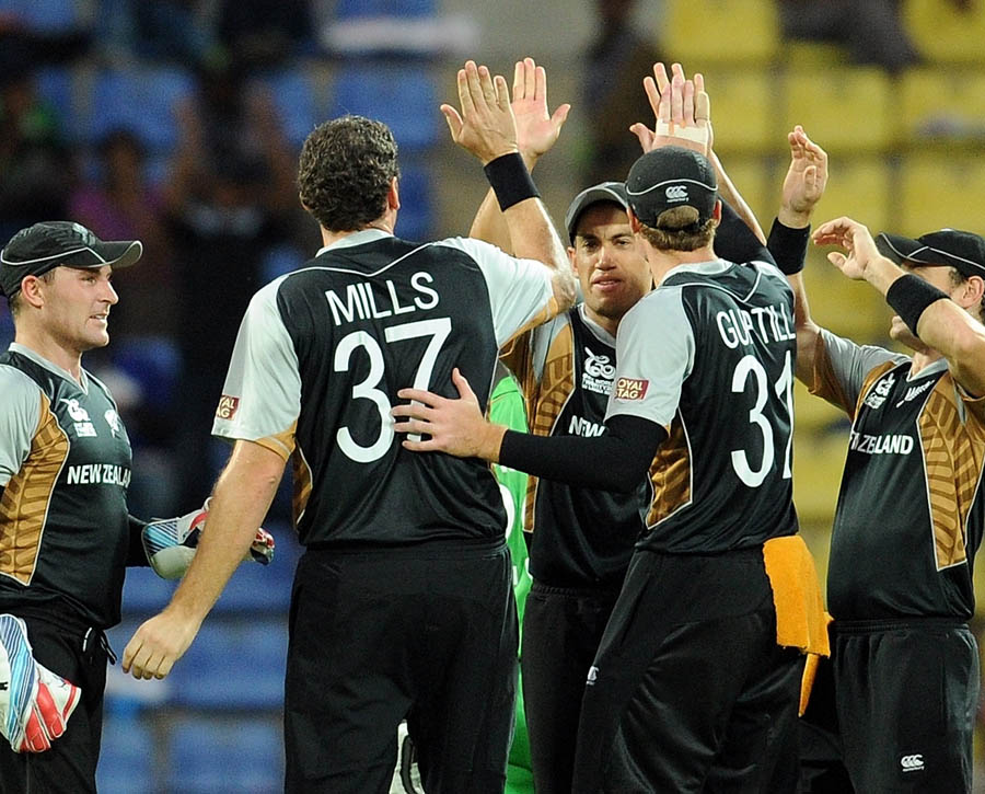 New Zealand cricketers celebrate the wicket of unseen Bangladesh batsman Tamim Iqbal