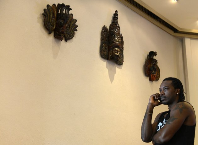 West Indies cricketer Chris Gayle talks on the phone at a hotel lobby