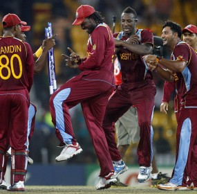 West Indies' cricketer Chris Gayle, center, dances with teammates to celebrate their win over Australia